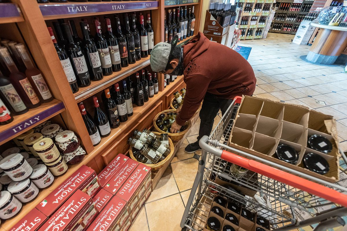 A worker restocks the shelves in the San Antonio Winery showroom