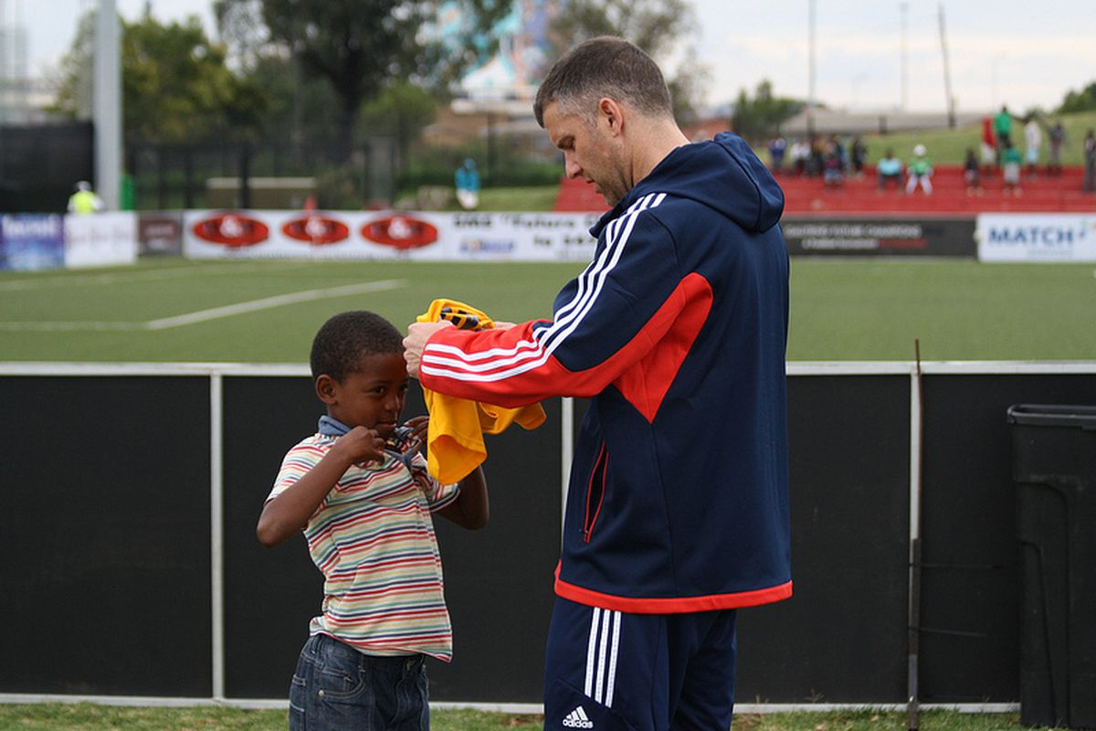 New England Revolution Director of Youth Development Bryan Scales giving away some gear to a local child at this Spring's Future Champions' Gauteng tournament in South Africa.