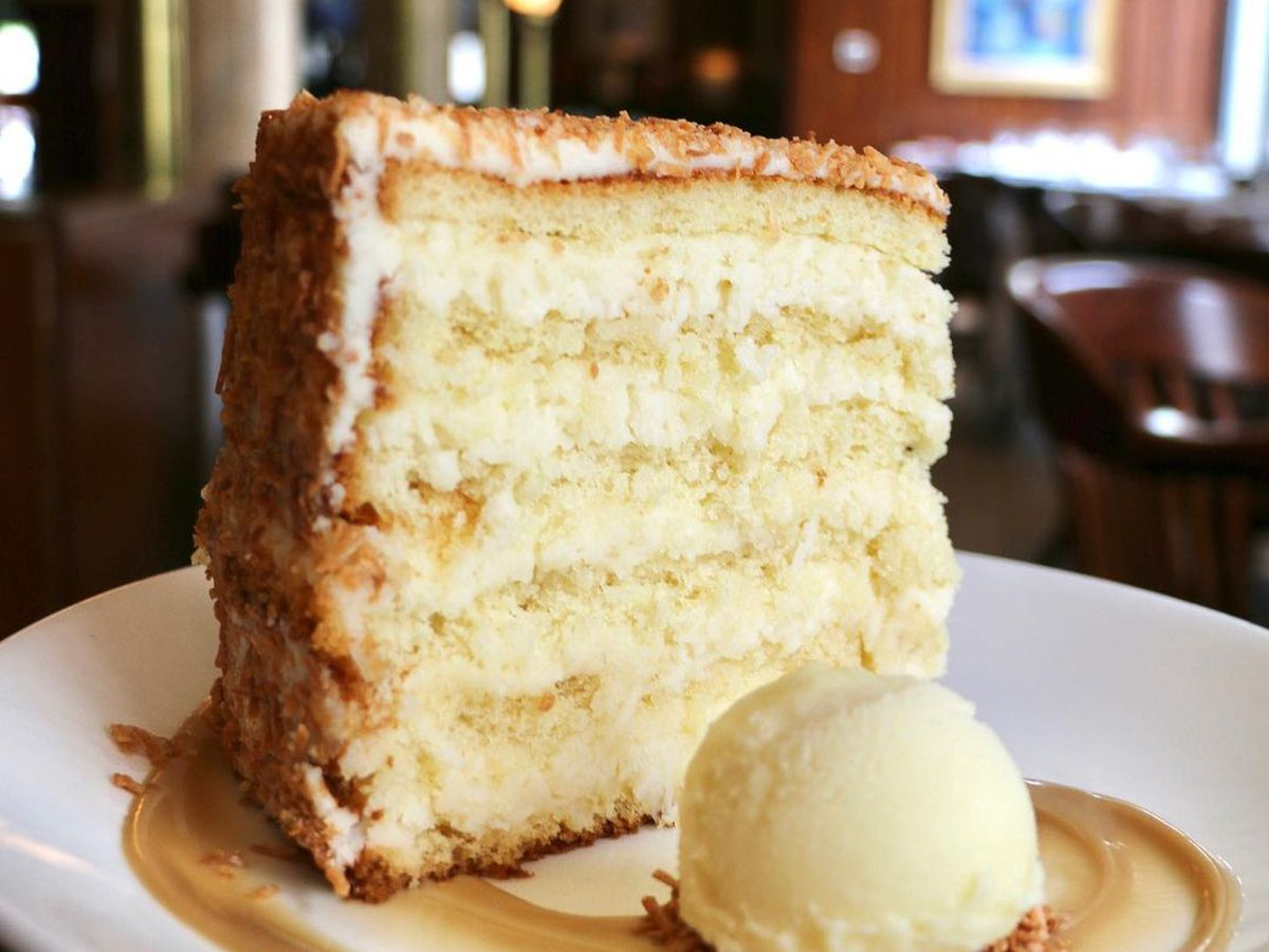 A tall slice of coconut layer cake sits on a plate with a scoop of ice cream next to it. An upscale restaurant dining room is visible in the background.