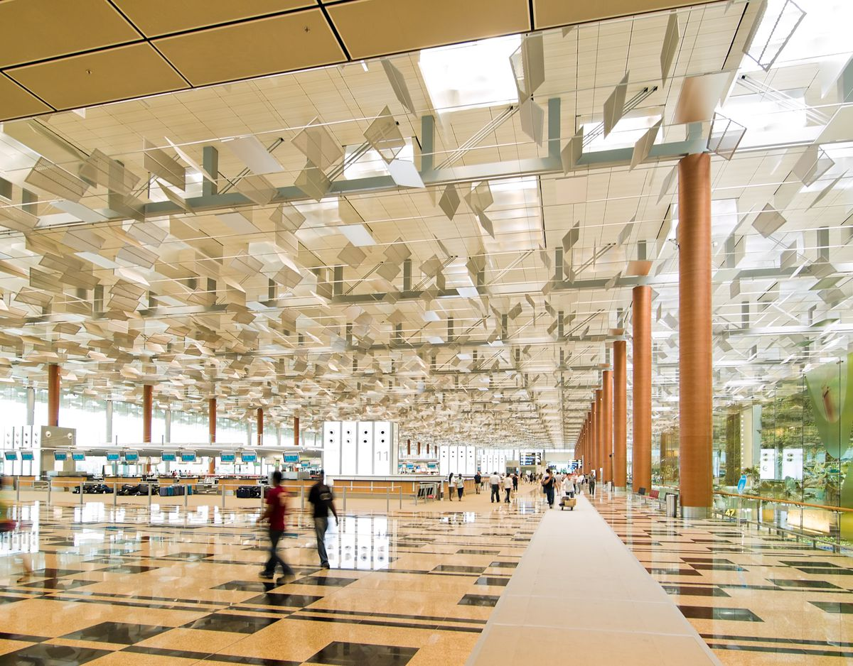 The exterior of Changi Airport in Singapore. The steel and glass ceiling has multiple skylights. The floor is tiled with yellow and black patterned tiles.