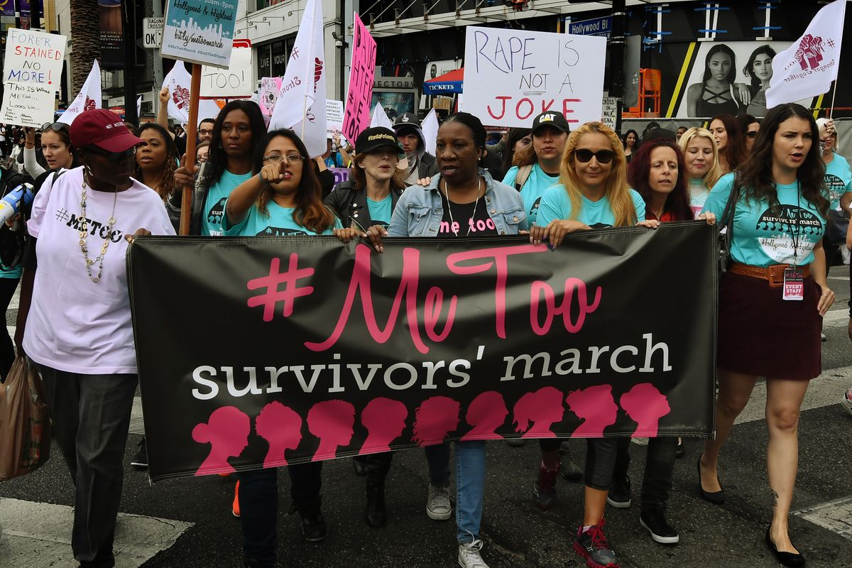 """Activists marching in Hollywood hold a banner that reads, """"#MeToo survivors' march."""""""