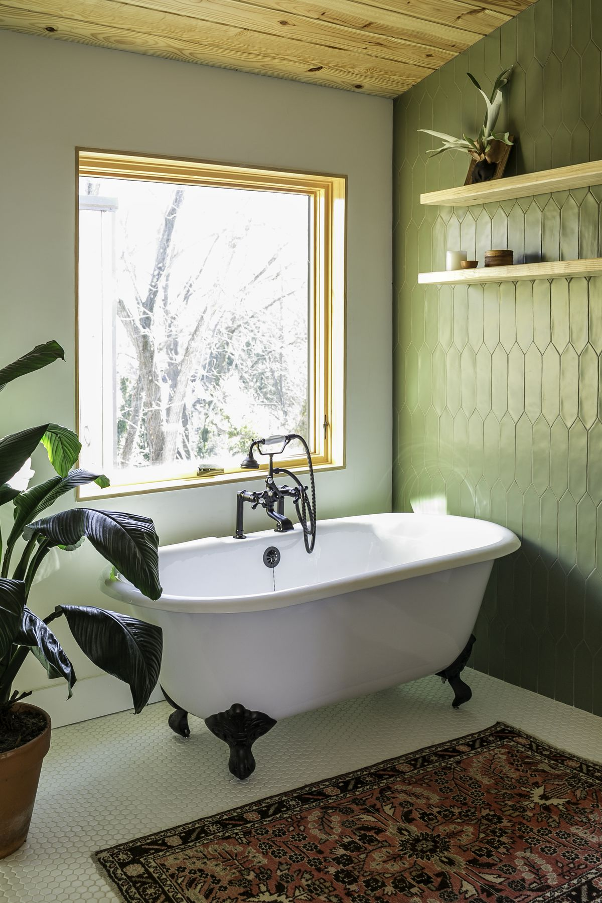 A stand alone tub in the bathroom in front of a very large square window. The bathroom has a wall of green tile, and there is a carpet in front of the tub, with a large plant.