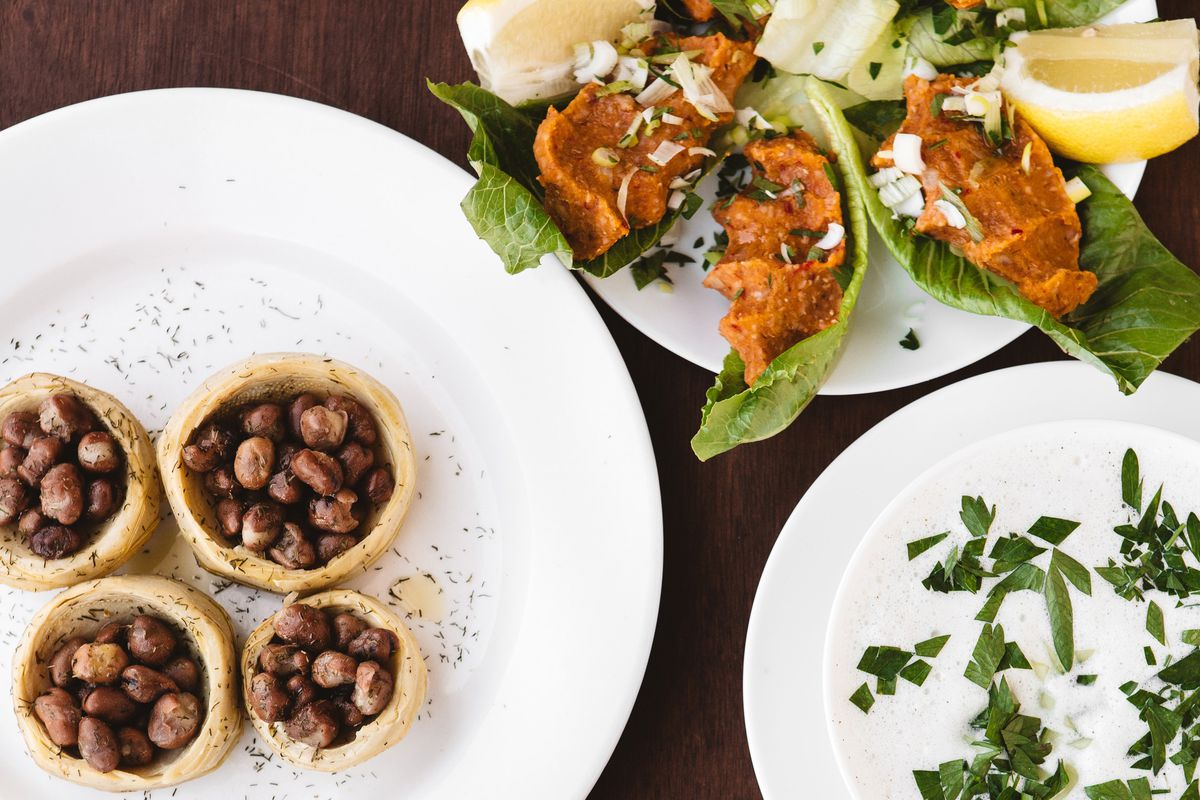 Three white plates sit on a brown table, including a bowl of a white liquid, small tartlet-like pastries, and lettuce cups filled with a bright-orange filling.
