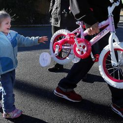 Charity Andrus follows closely as a new bicycle is brought to her car during the 2014 Operation Chimney Drop at Head Start in Salt Lake City, Monday, Dec. 15, 2014.
