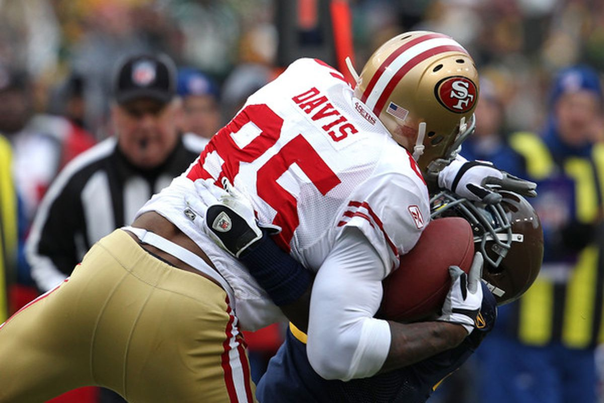 GREEN BAY WI - DECEMBER 05: Vernon Davis #85 of the San Francisco 49ers catches a pass over Charlie Peprah #26 of the Green Bay Packers at Lambeau Field on December 5 2010 in Green Bay Wisconsin. (Photo by Jonathan Daniel/Getty Images)