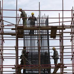 Workers stand on scaffolding at a road construction site in Beijing Thursday, April 12, 2012. China's economic growth fell to its lowest level in nearly three years in the first quarter of 2012 amid weak trade and lending controls.