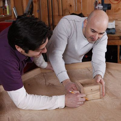 Two people working together to mark the pieces on a DIY poker table.