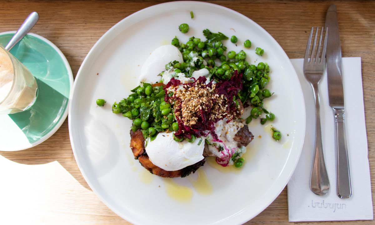 A white plate with a poached egg dish piled with peas, shredded beet, and sprinkled with seeds