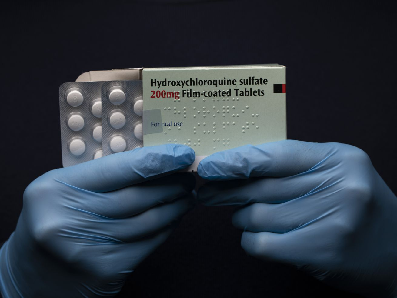 Hands holding ups package of Hydroxychloroquine Sulfate medication.