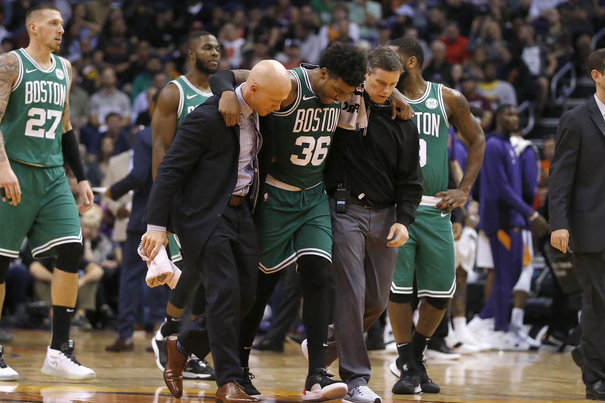 Boston Celtics guard Marcus Smart gets helped off the court in the second half of an NBA game against the Phoenix Suns at Talking Stick Resort Arena.