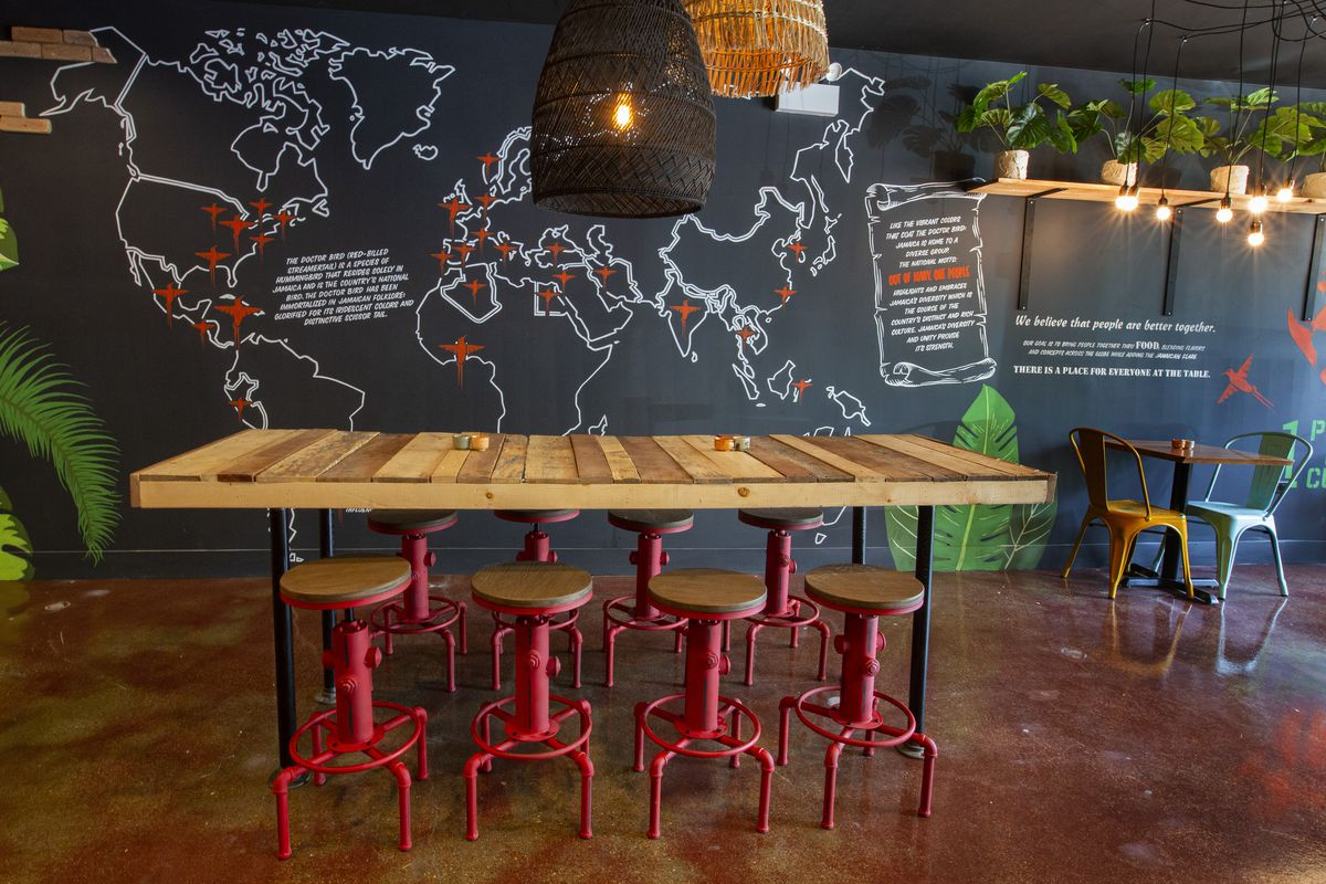 A restaurant interior with a wood floor and black walls painted with a map of the world. There is a tall wooden table with eight red stools.