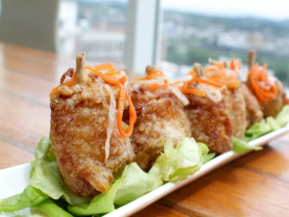 Four studs of golden-fried chicken wings sit on butter lettuce leaves with shreds of carrots and radish on top.