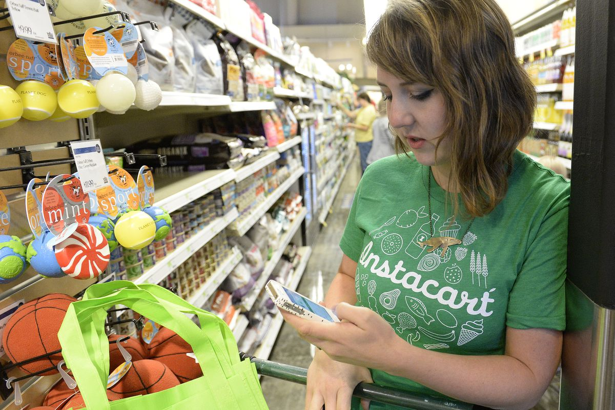 Kaitlin Myers a shopper for Instacart studies her smart phone as she shops for a customer at Whole Foods in Denver. Myers receives a grocery list for a shopper and then completes the shopping on Tuesday, October 28, 2014.