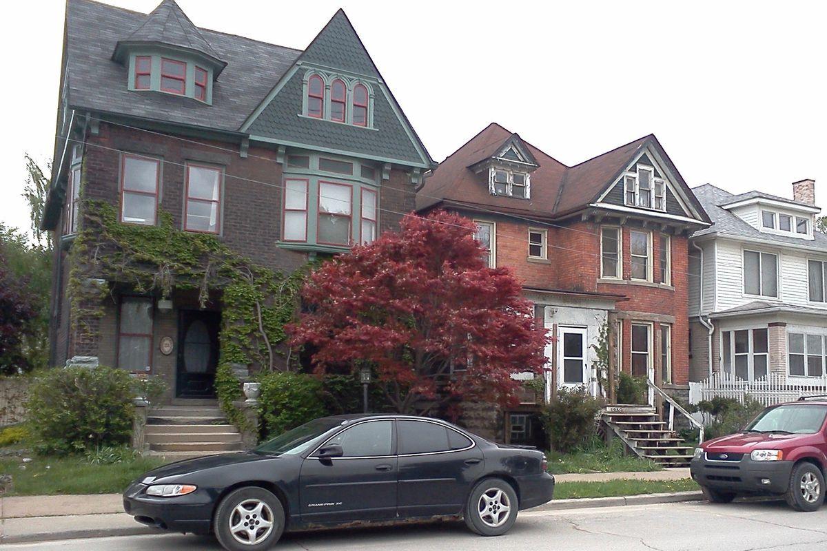 Three, three-story brick homes on a residential street.