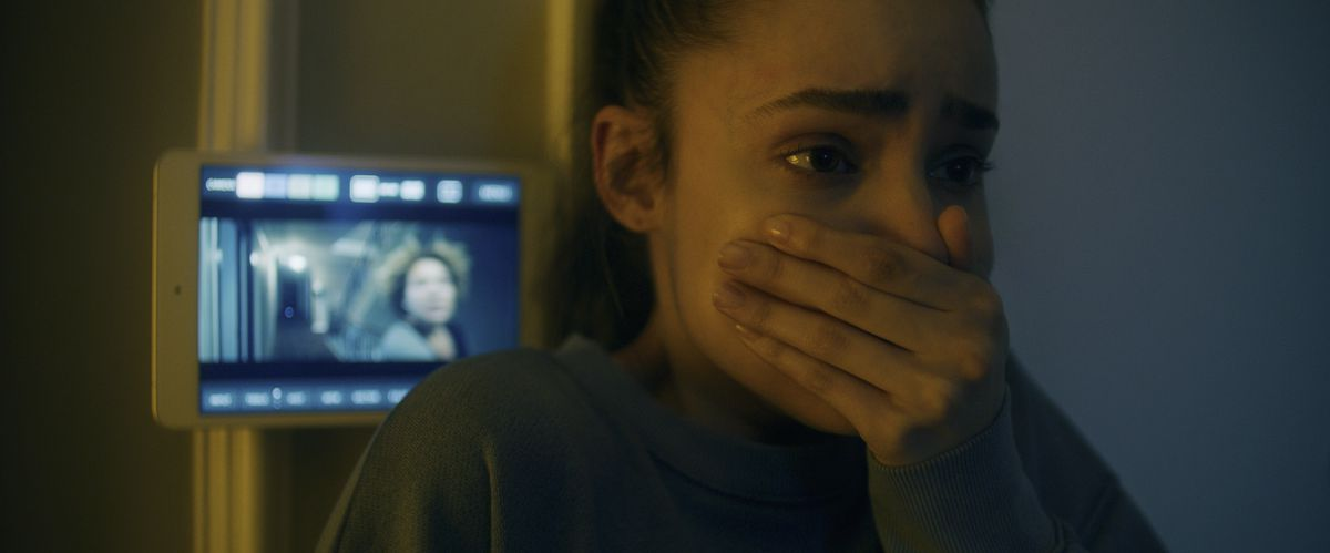 Sofia Carson gasps in horror with.a security camera feed behind her in Songbird