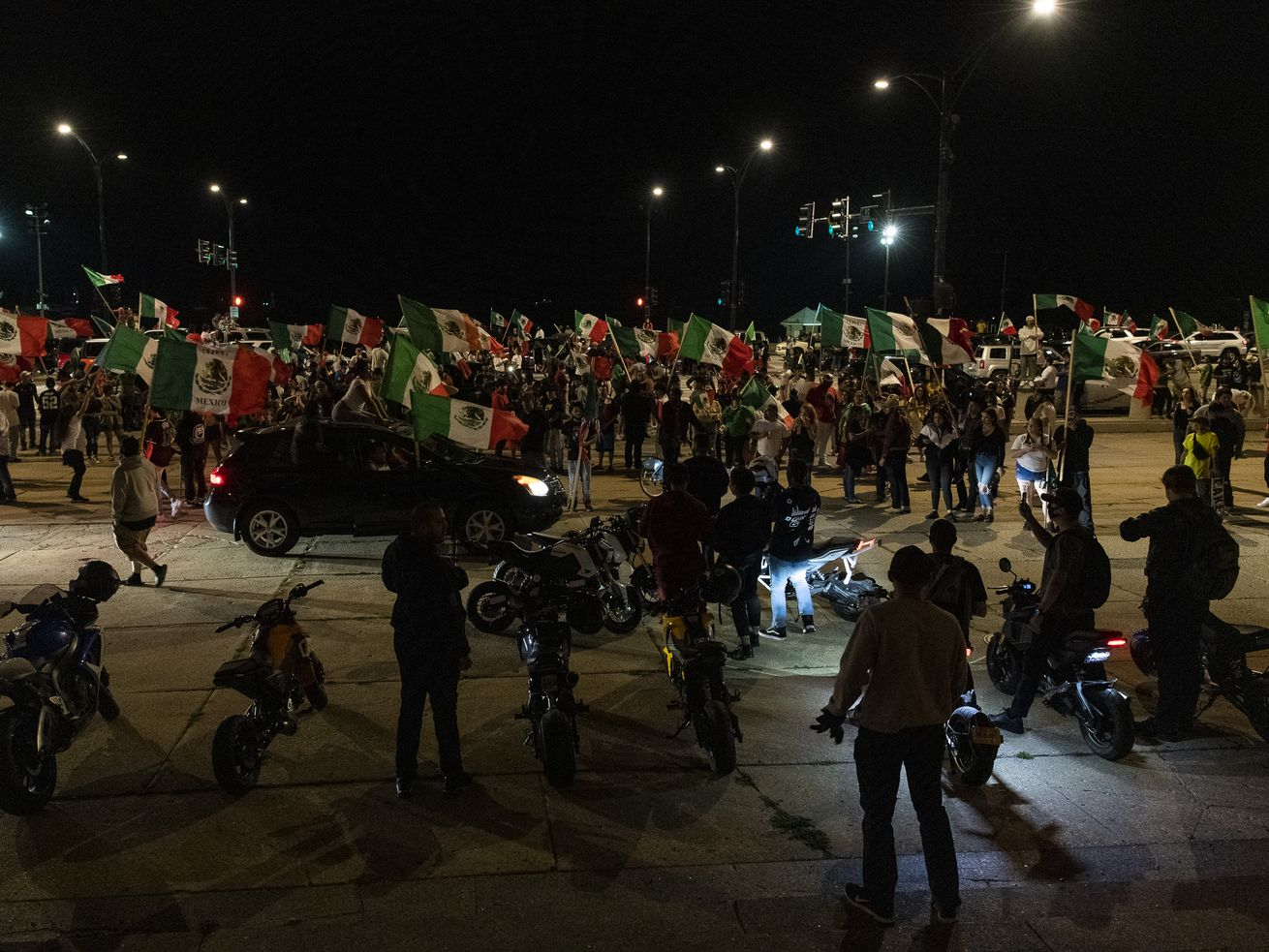 People dance and party on Lake Shore Drive near Buckingham Fountain, as hundreds celebrate Mexico's Independence Day, Wednesday, Sept. 16, 2020.