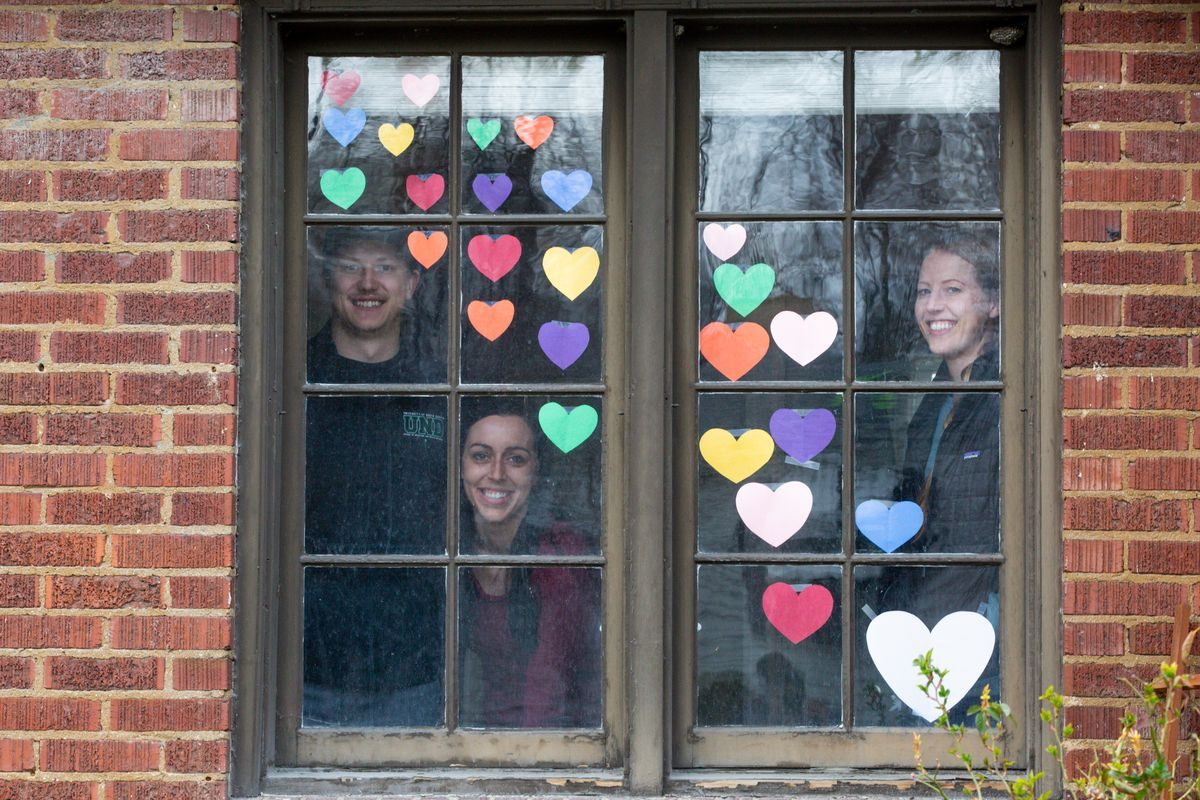"""Nolan Schwartz, Megan Schwartz and Katie Schwartz pose for a portrait inside their Sugar House home on Thursday, March 26, 2020. Katie Schwartz spotted the trend of taping paper hearts on windows on Facebook. """"It's just to let neighbors and passersby know that we're all in this together,"""" she said."""