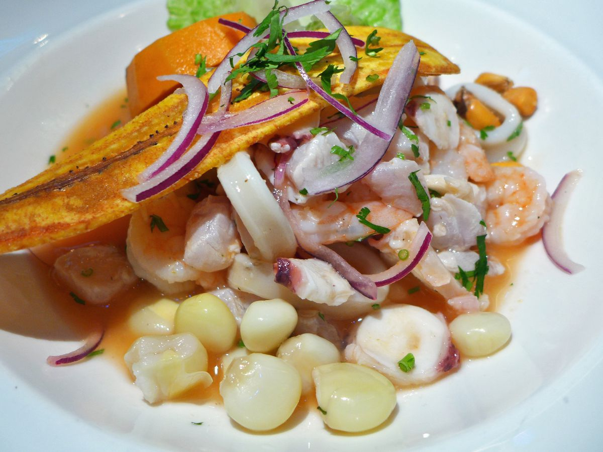 Corn, plantain chips, and purple onions join shrimp and other seafood in an orange fluid in a bowl.