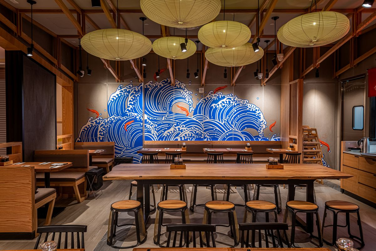A blue wave logo on a far wall at a ramen restaurant with lots of wood.