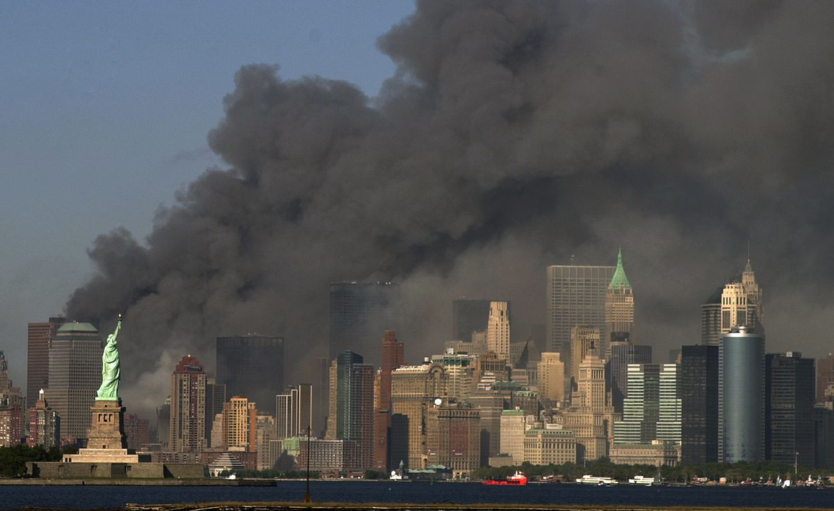 In this Tuesday, Sept. 11, 2001 file photo, thick smoke billows into the sky from the area behind the Statue of Liberty, lower left, where the World Trade Center towers stood.