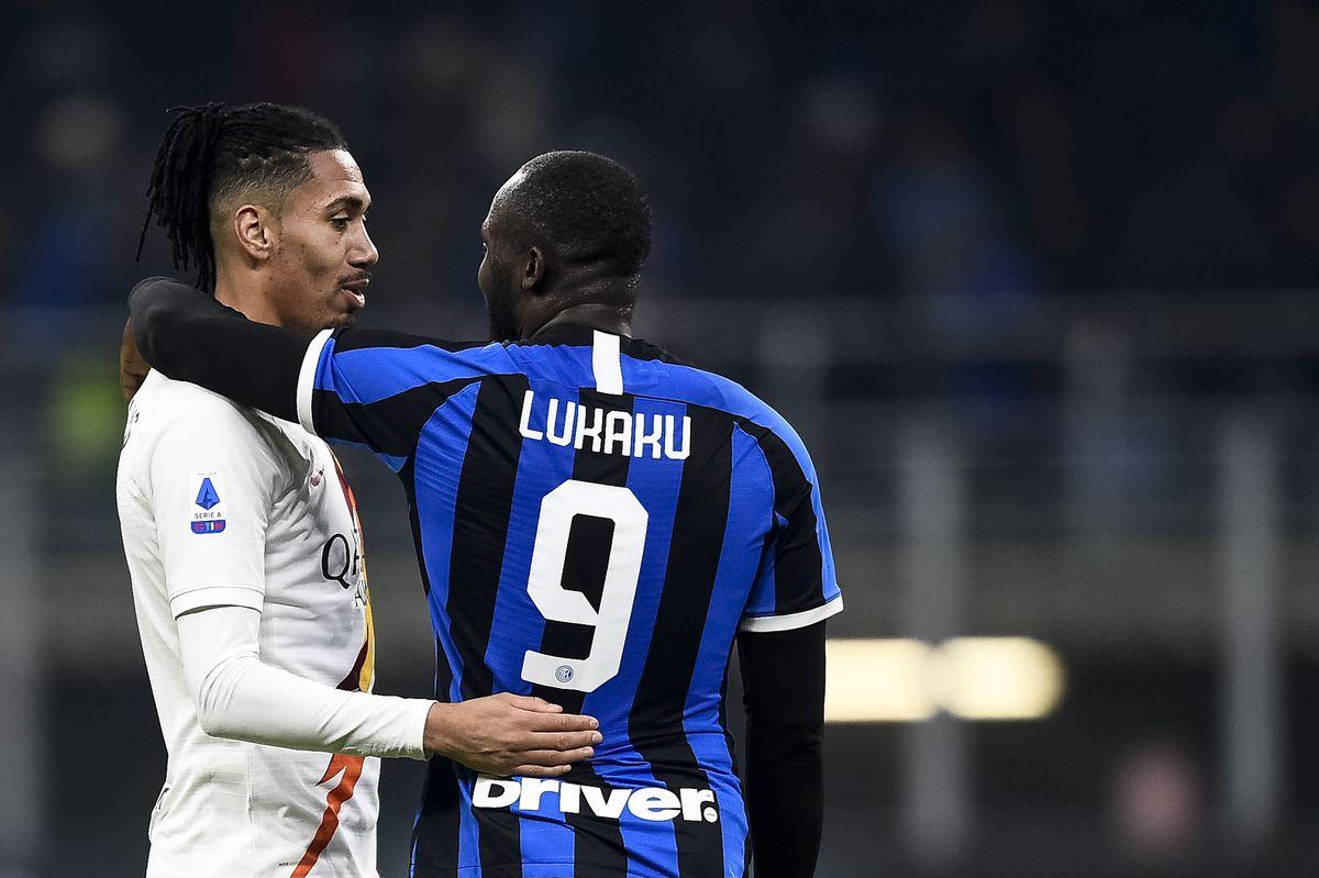 Chris Smalling (L) of AS Roma hugs Romelu Lukaku of FC...
