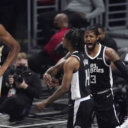Los Angeles Clippers guard Terance Mann, center, celebrates with guard Paul George, right, after scoring and drawing a foul as Utah Jazz center Rudy Gobert stands by during the first half in Game 6 of a second-round NBA basketball playoff series Friday, June 18, 2021, in Los Angeles.
