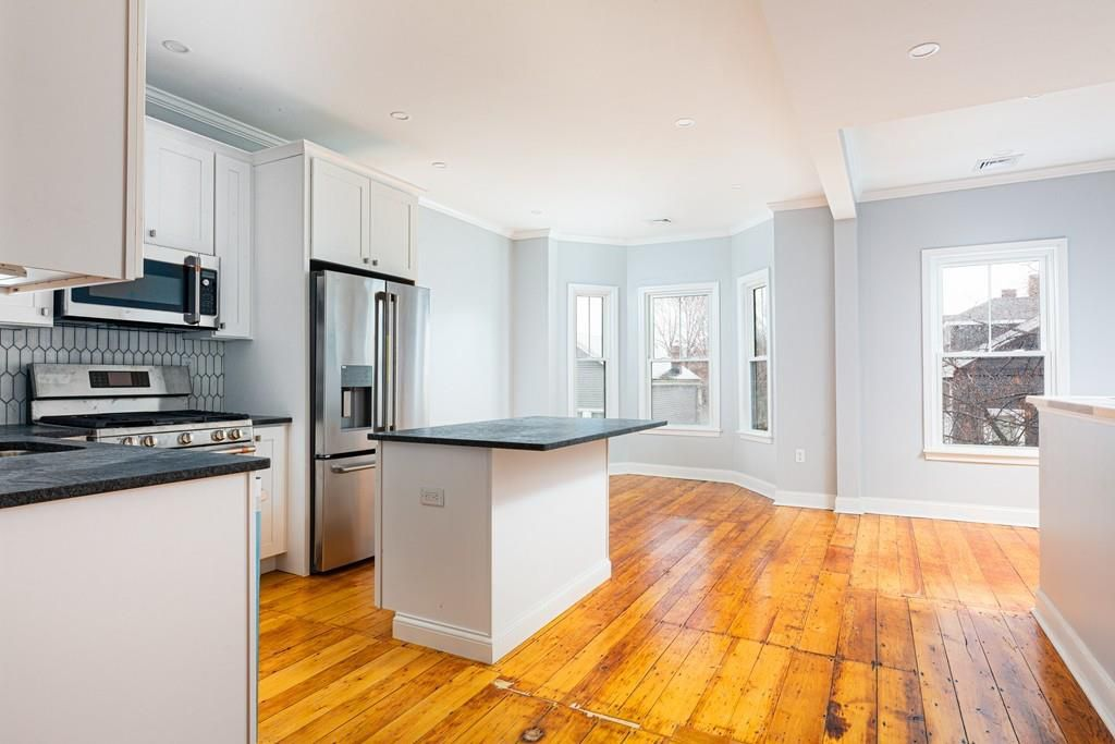 An open and empty kitchen and dining room area with an island featuring prominently.