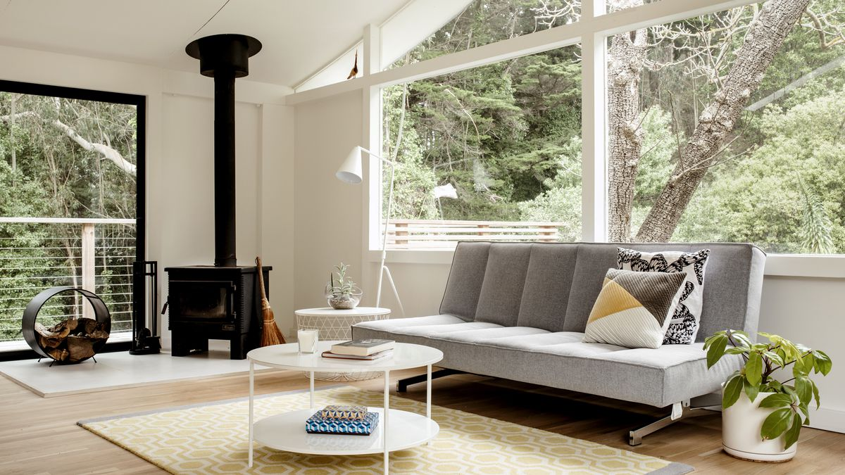 A living area. There are large windows overlooking trees. There is a large grey couch with multiple assorted pillows. There is a black fireplace in one corner of the room. There is a white coffee table and a houseplant in a white planter.