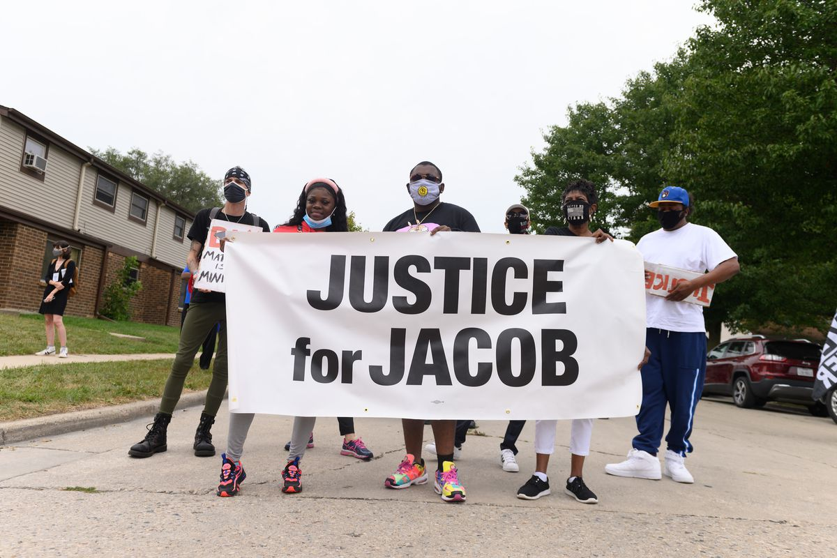 """Five Black protesters in masks hold a giant white banner in the middle of a tree-lined street that reads """"Justice for Jacob."""""""
