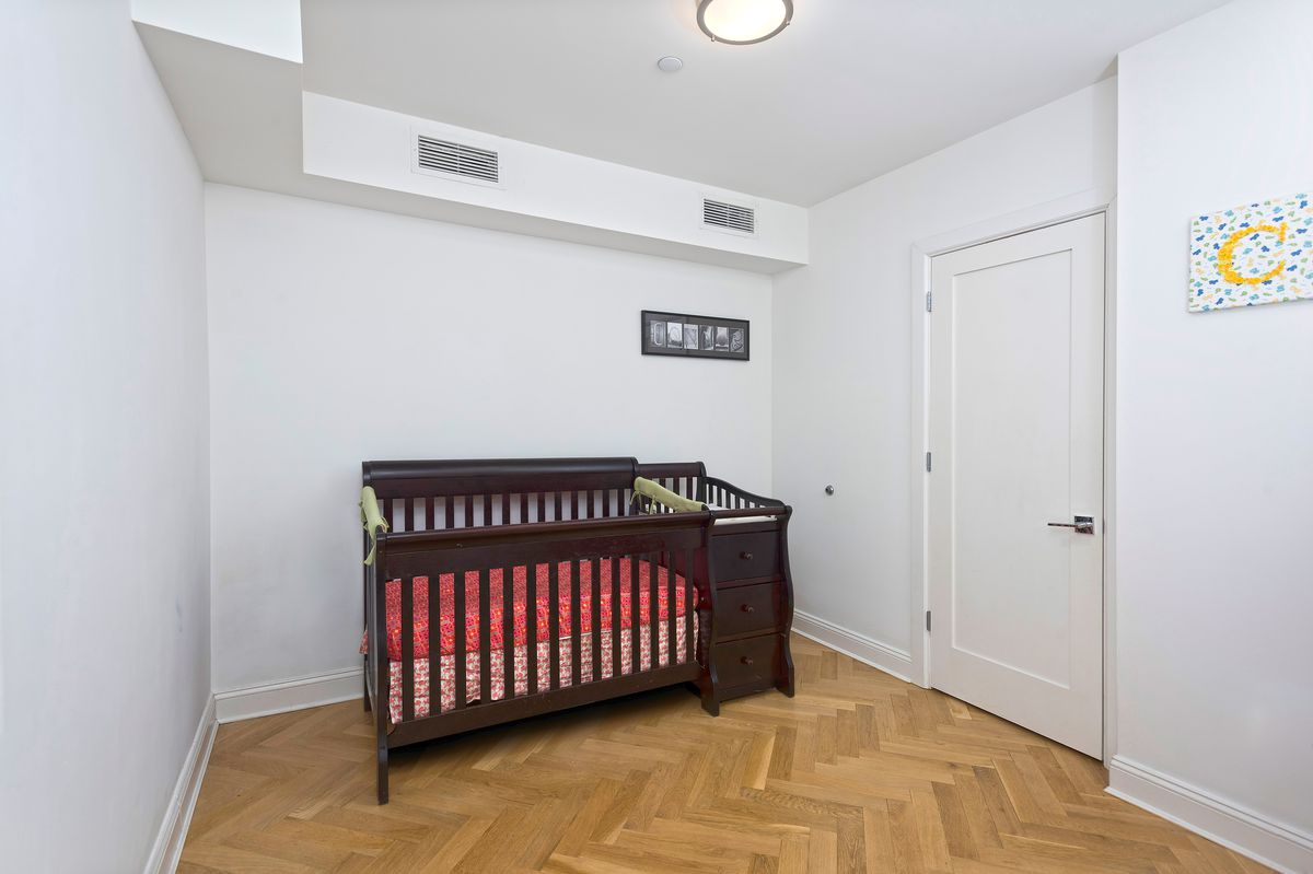 A nursery room with a crib, white walls, and hardwood floors.