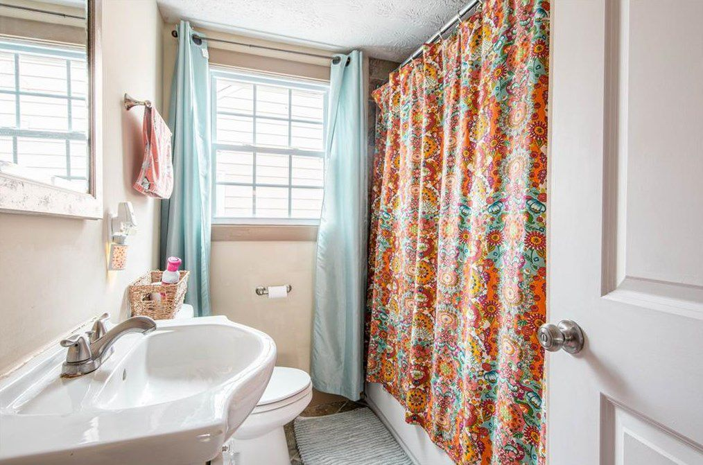 A long beige bathroom, with a floral shower curtain.