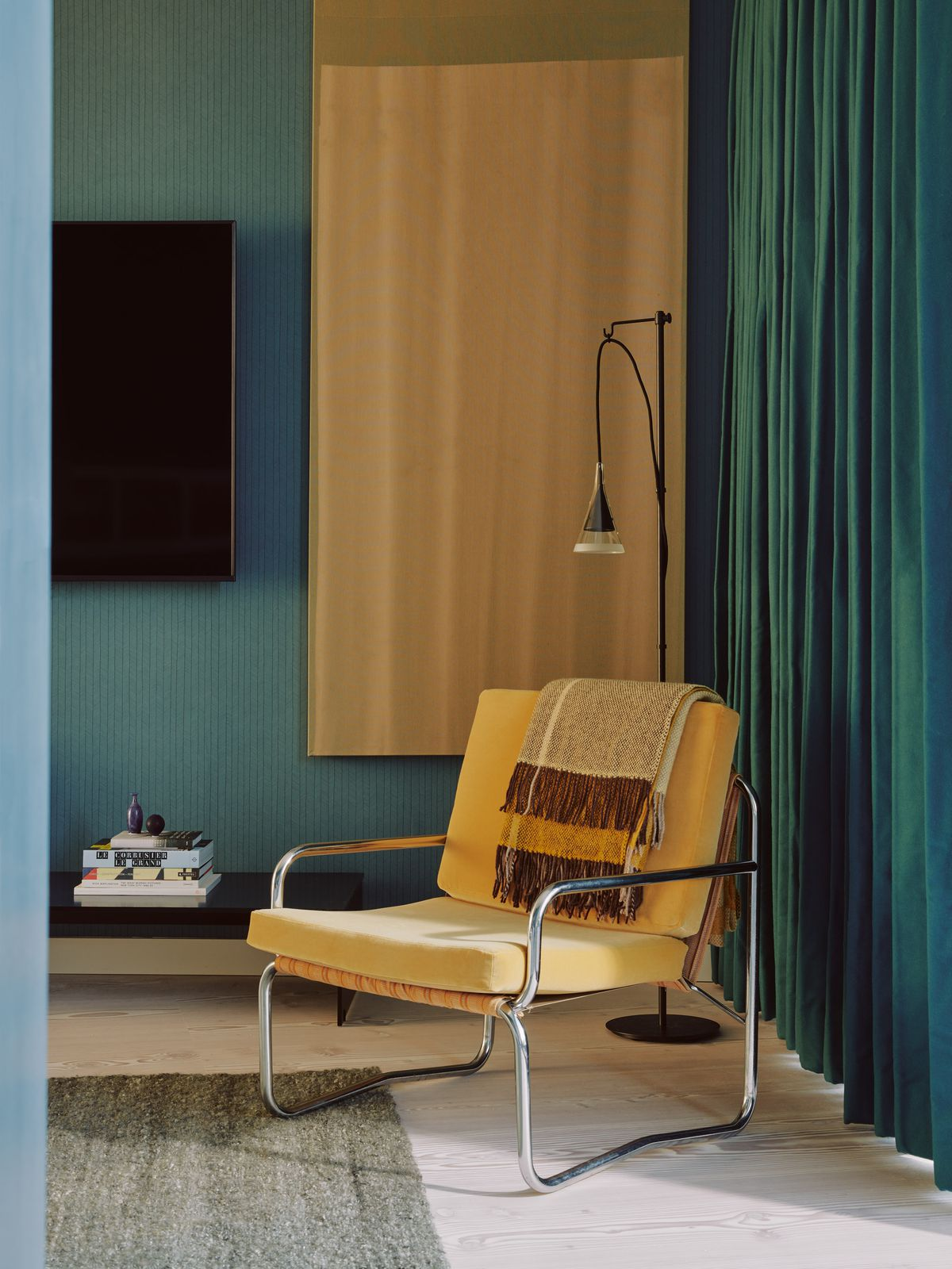 A yellow armchair in front of teal curtains.