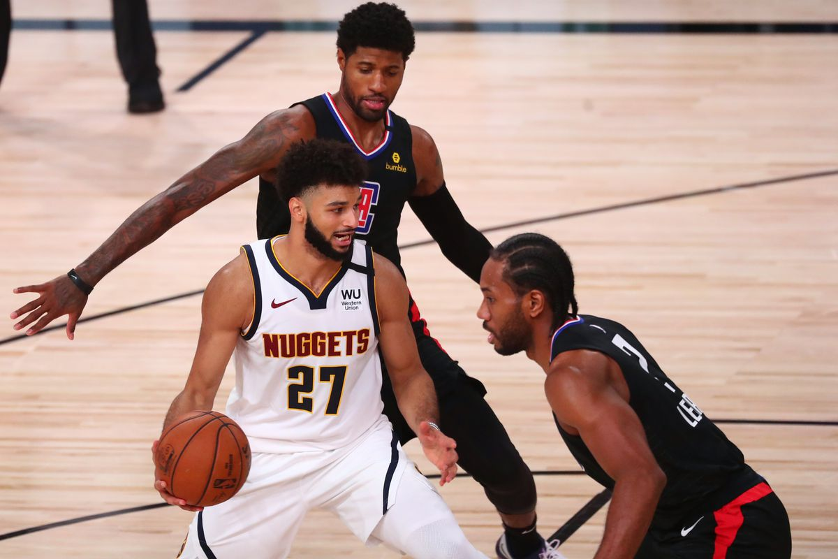 Denver Nuggets guard Jamal Murray handles the ball while Los Angeles Clippers guard Paul George  and forward Kawhi Leonard during the first half in game seven of the second round of the 2020 NBA Playoffs at ESPN Wide World of Sports Complex.