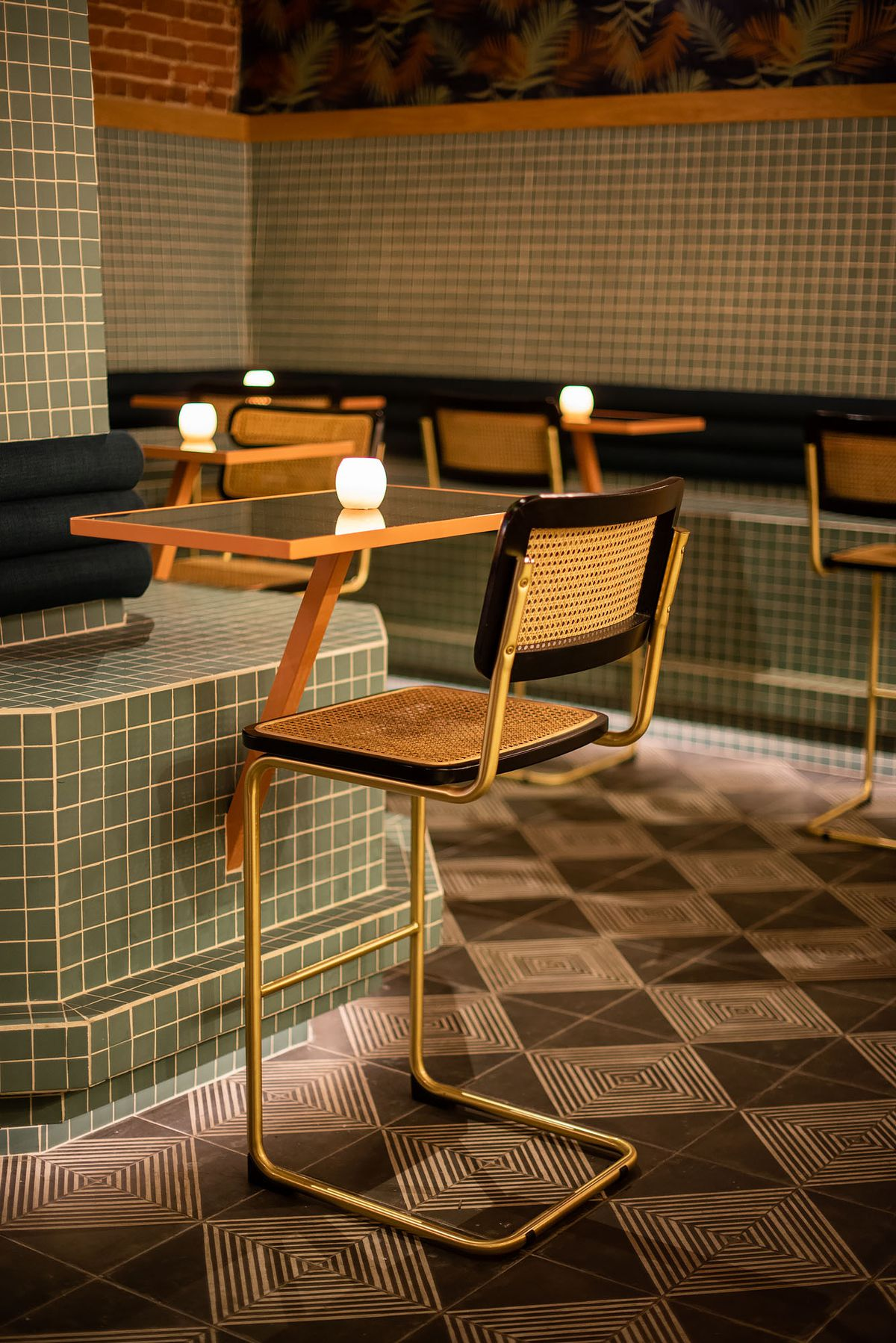 A wicker bar stool for one at a moody cocktail bar.