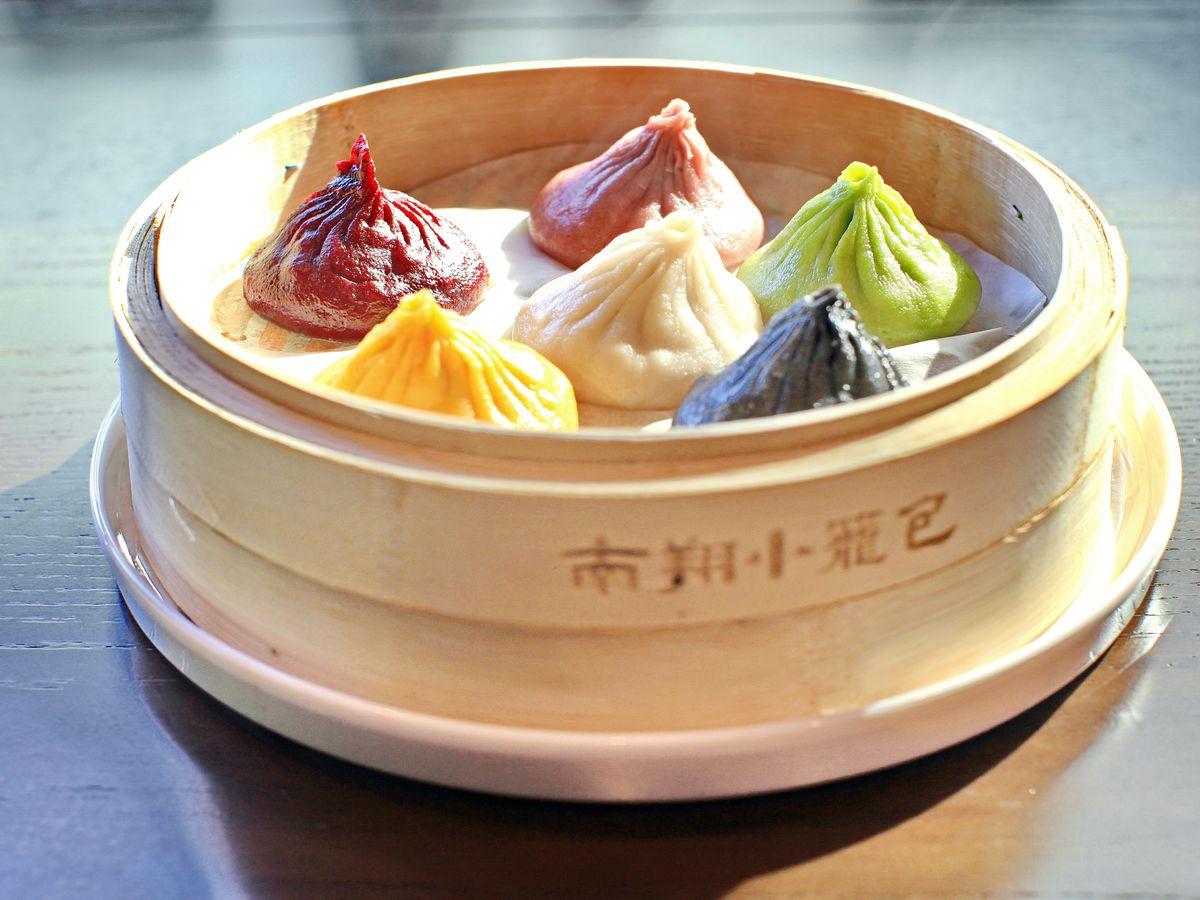Six multi-colored soup dumplings in a bamboo steamer at Nan Xiang Xiao Long Bao