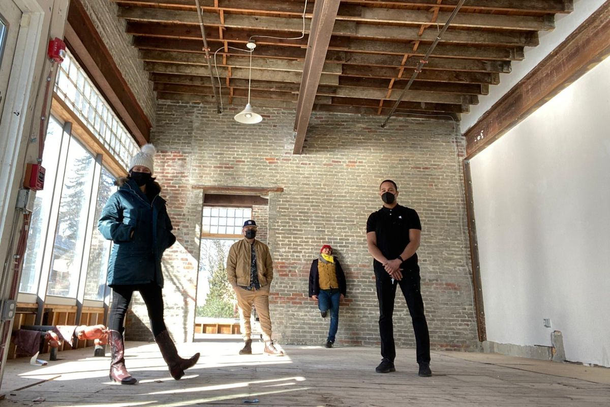 Four people wearing face masks and casual clothing stand in an unfinished space with nearly floor-to-ceiling windows on one side and lots of exposed beams and brick