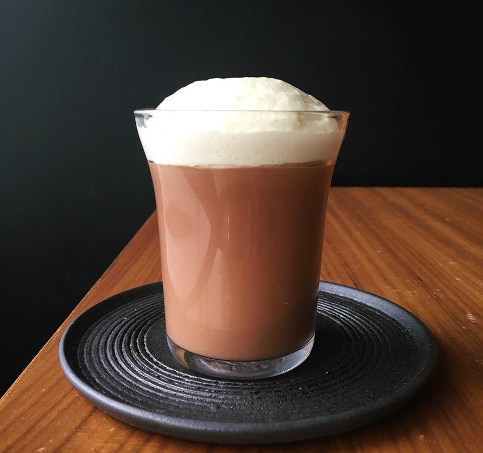 A foam-topped hot chocolate in a glass.