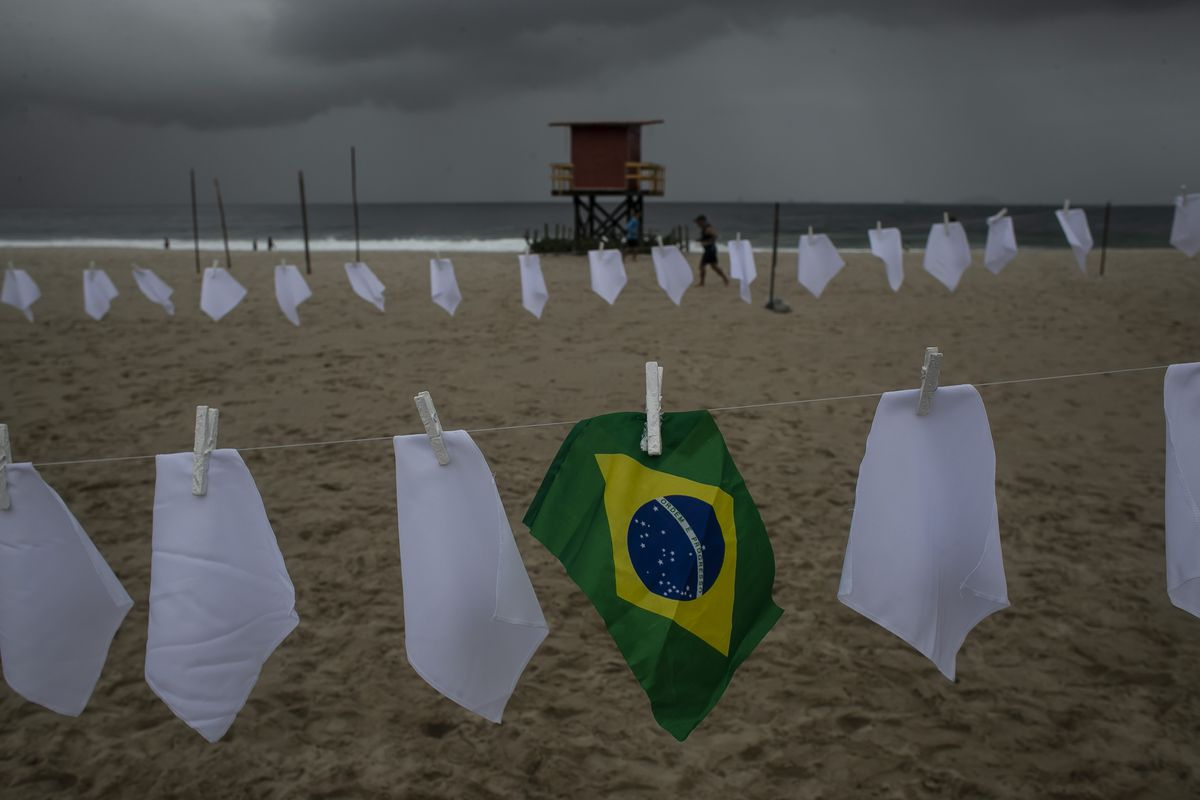 """A Brazilian flag hangs on a clothesline on Copacabana beach amid white scarves that represent those who have died of COVID-19 in Rio de Janeiro, Brazil, Friday, Oct. 8, 2021. The action was organized by the NGO """"Rio de Paz"""" to protest the government's handling of the pandemic as the country nears a total of 600,000 COVID-19 related deaths."""