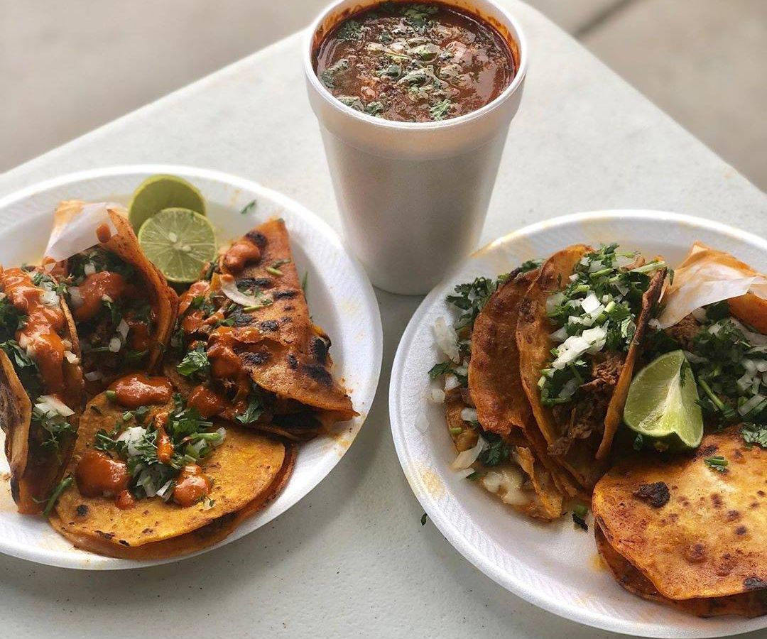 Two plates filled with tacos with a cup of broth