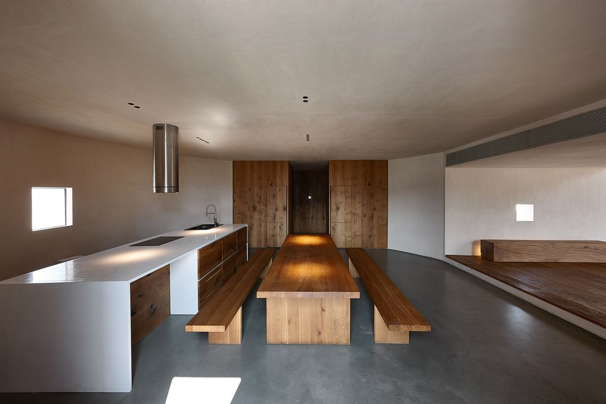 Long wooden table in kitchen with polished concrete floors.