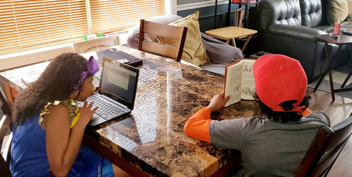 Brook and Jake Tunstill do schoolwork at their family's kitchen table at their home on Chicago's South Side.