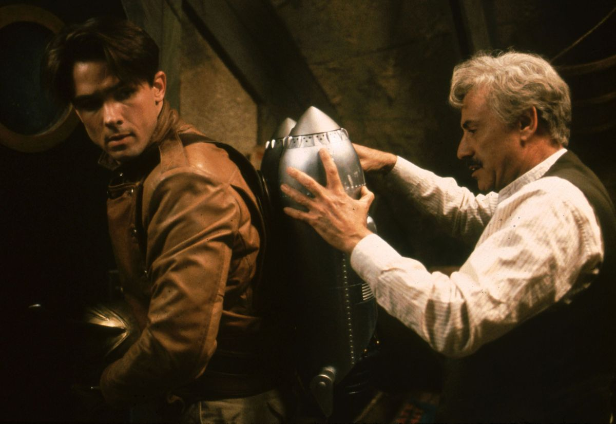 Alan Arkin affixing a jetpack to Billy Campbell's back.