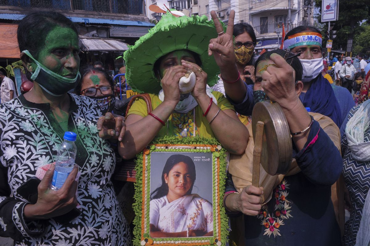 Supporters of Trinamool Congress party chief Mamata Banerjee holding an earlier photograph of her celebrate early lead for the party in the West Bengal state elections in Kolkata, India, Sunday, May 2, 2021.