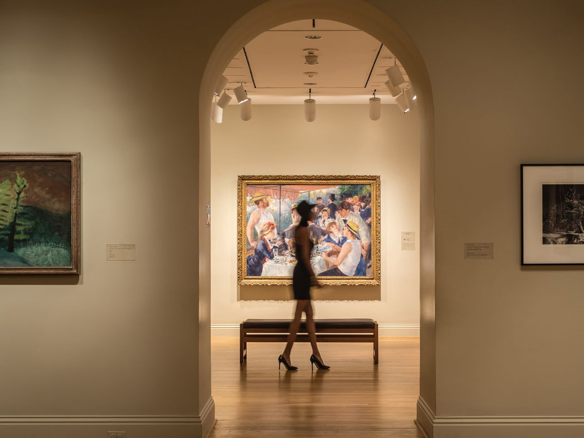 The interior of the Phillips Collection in Washington D.C. There are works of art hanging on the wall and an arched doorway.