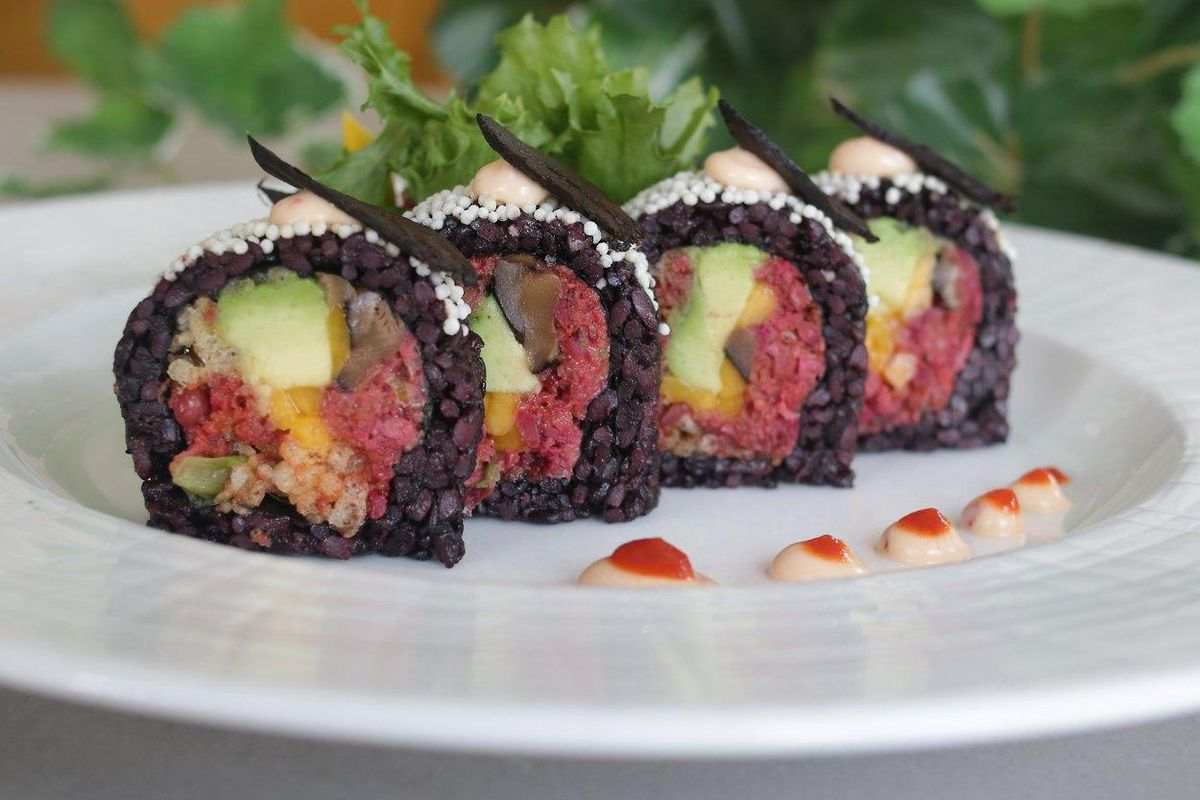 Black rice sushi on a white plate.