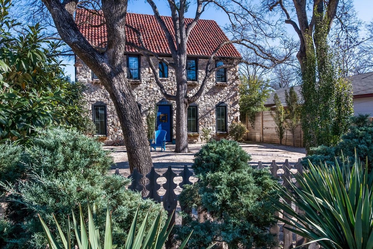 Two story stone house with red clay tile roof, large front yard with drought-tolerant plants and picket fence in front