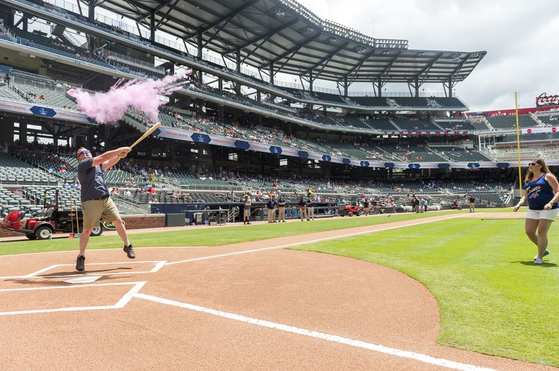 A man at home plate on a baseball diamond swings a bat at a ball that explodes in pink smoke.