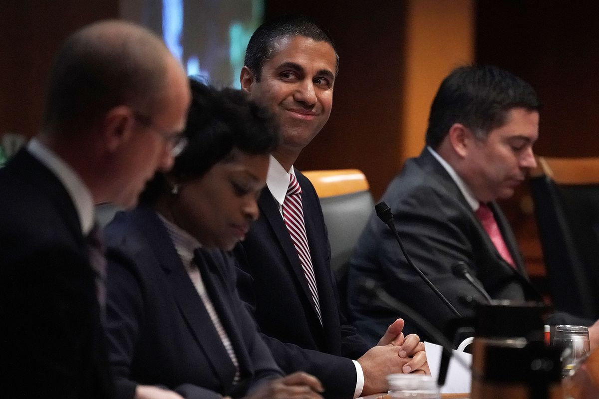 Federal Communications Commission Chairman Ajit Pai (3rd L) smiles during a commission meeting December 14, 2017 in Washington, DC. FCC has voted to repeal its net neutrality rules at the meeting.