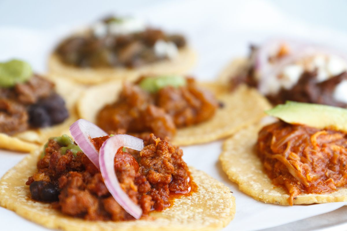 A platter of small tacos with various braises inside.