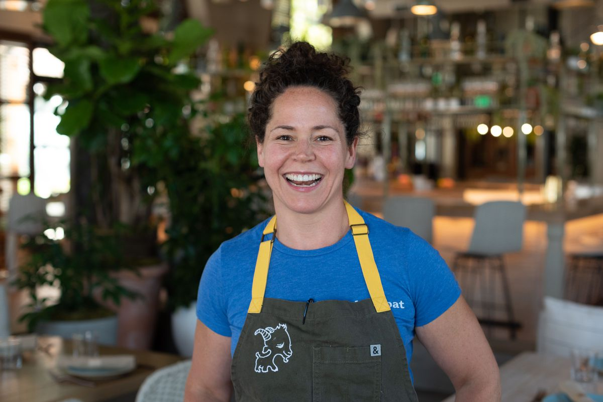 A chef in a blue t-shirt and green apron smiles for the camera.